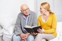 daughter reading to her elderly dad